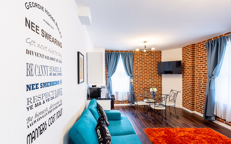 An aparment layout with a bright blue sofa, wooden floor and brick walls