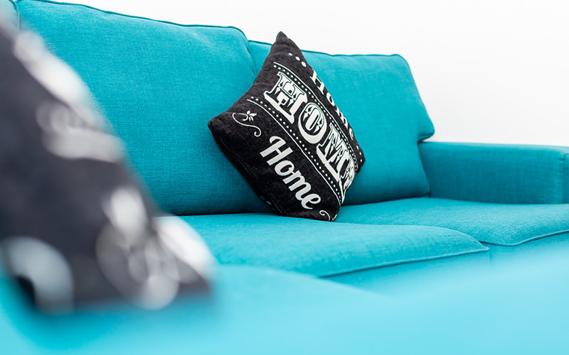 A close up of a black cushion on a brightly coloured sofa