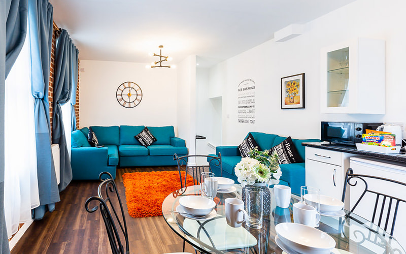 An aparment layout with a bright blue sofa, wooden floor, brick walls and a small glass dining table