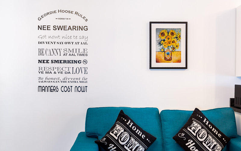 A wall mural featuring geordie phrases