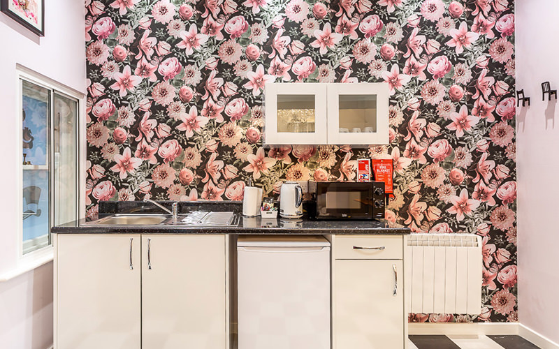A small kitchen with a floral wall feature