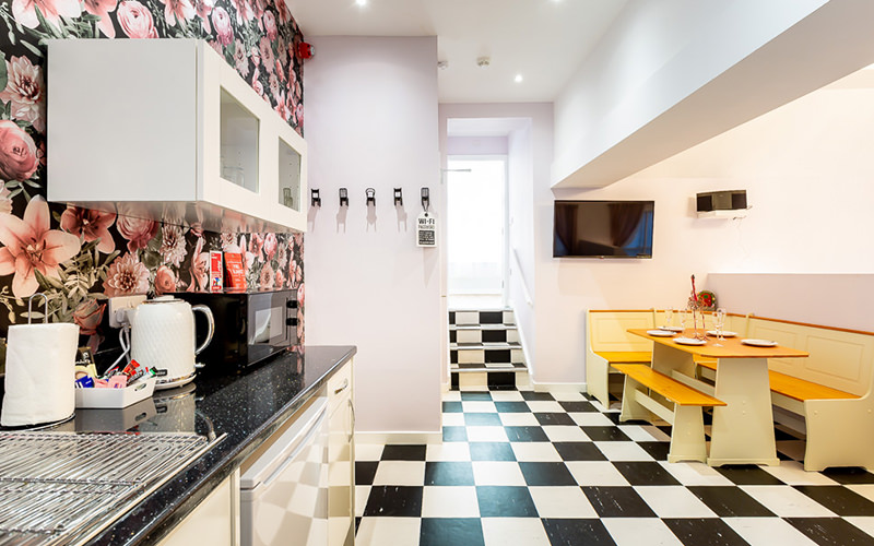 A small kitchen with a floral wall feature and a chequered floor