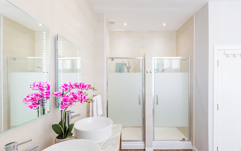 A bathroom with two flowers, two sinks and a vase containing flowers