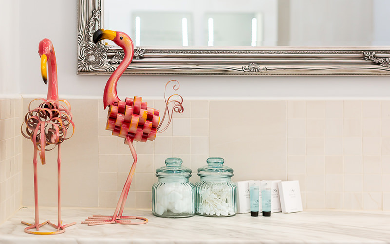 Two flamingo styled decorations sitting on top of a bathroom bech