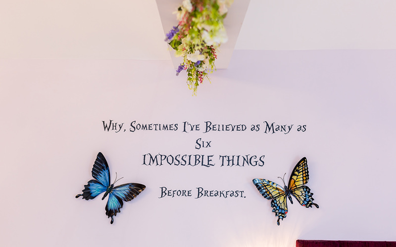A wall mural with two large butterflies and quote from alice in wonderland