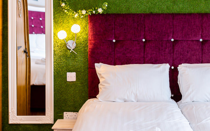 A close up of a double bed with a grass wall feature behind it