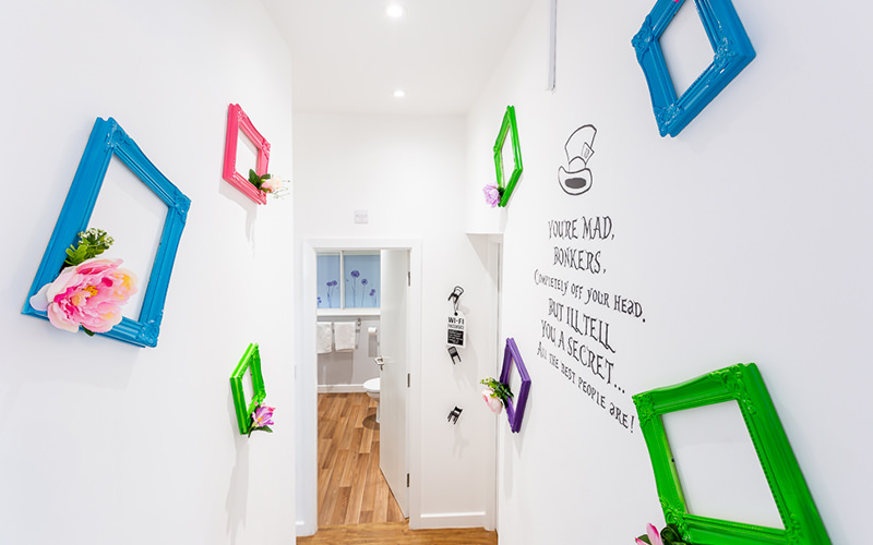 A white coridor with brightly coloured empty picture frames hanging on the walls and a quote from alice in wnderland