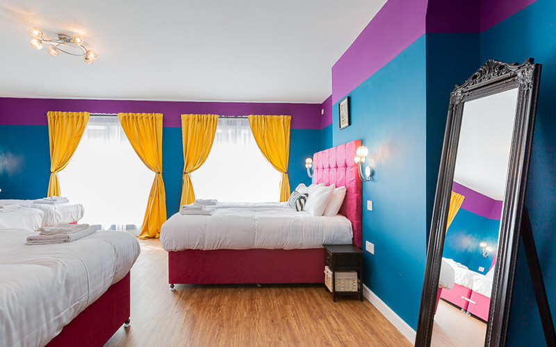 A purple and blue room with several large beds and bright yellow curtains