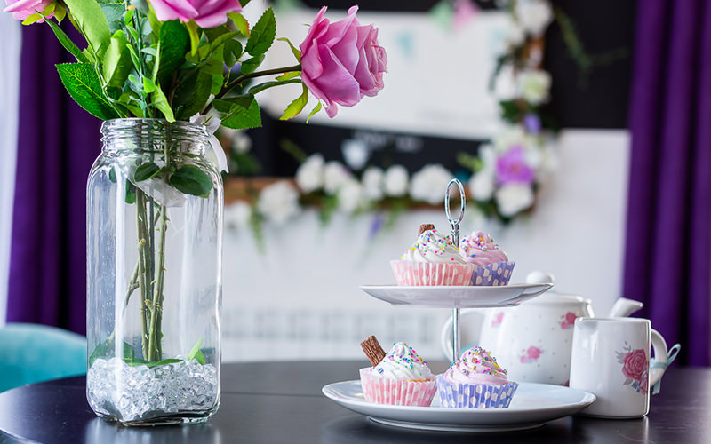 A close up of a table with a vase containing three pink roses and a tray of cupcakes
