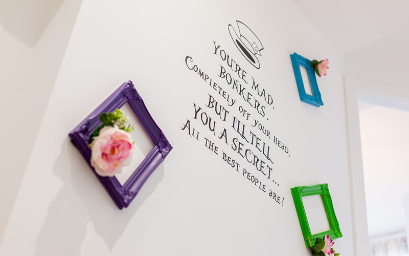 A wall mural featuring a quote from alice in wonderland and several brightly coloured photo frames