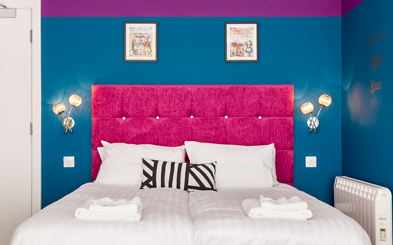 A double bed with striped cushions and a pink headboard