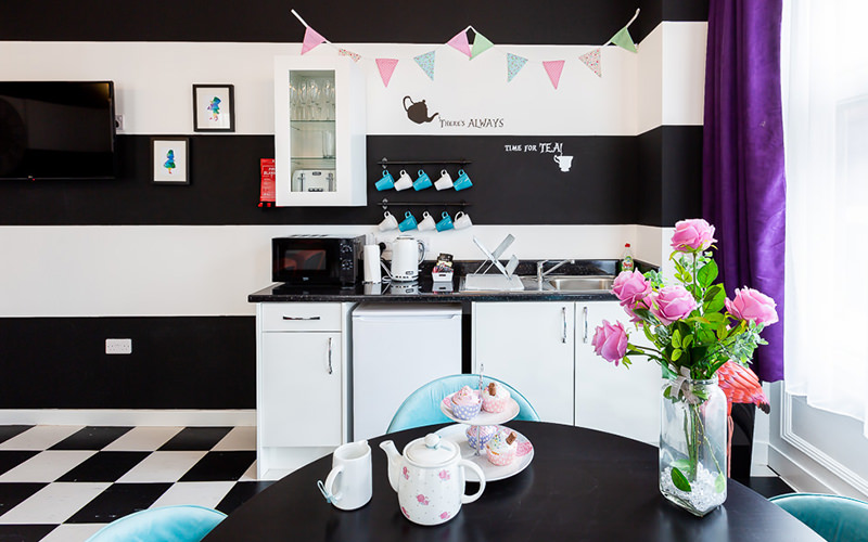 A black and white striped room with a chequered floor and bright furniture and kitchen facilities
