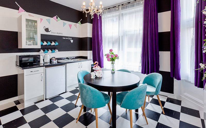 A black and white striped room with a chequered floor, dining table, bright furniture and kitchen facilities