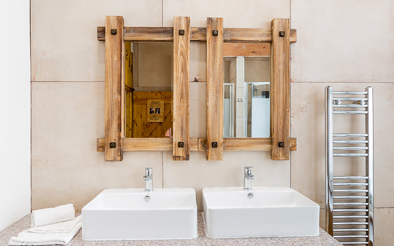 A close up view of two mirrors with wooden frames and two sinks