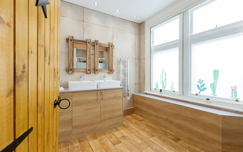 An apartment bathroom with wooden features
