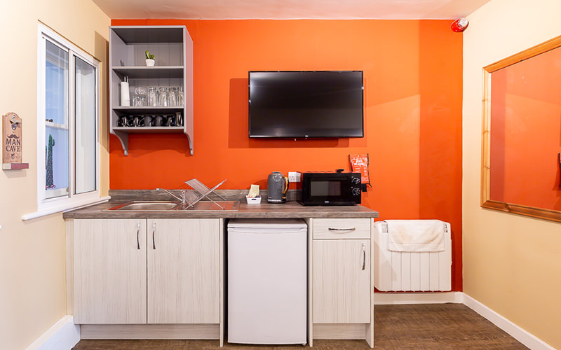A small kitchen with a bright orange wall and a TV