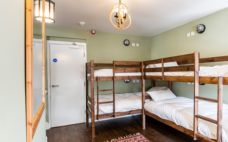An apartment rom with two bunk beds and a large mirror
