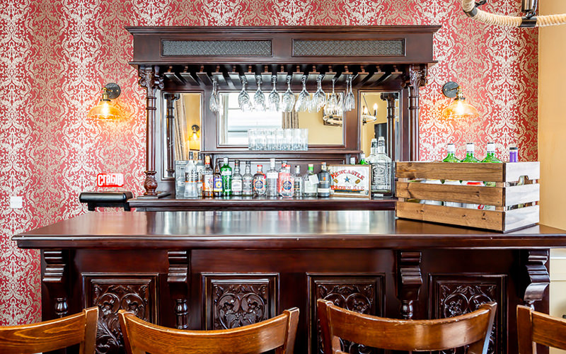 An old style western bar in an apartment with four wooden stools