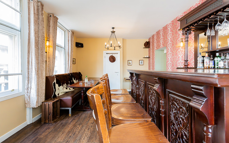 An old style western bar in an apartment with four wooden stools, a small dining table and a sofa