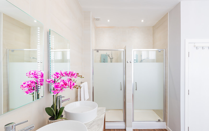An apartment bathroom with two showers and two small sinks