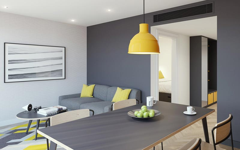 A grey and yellow themed room with a sofa and dining table