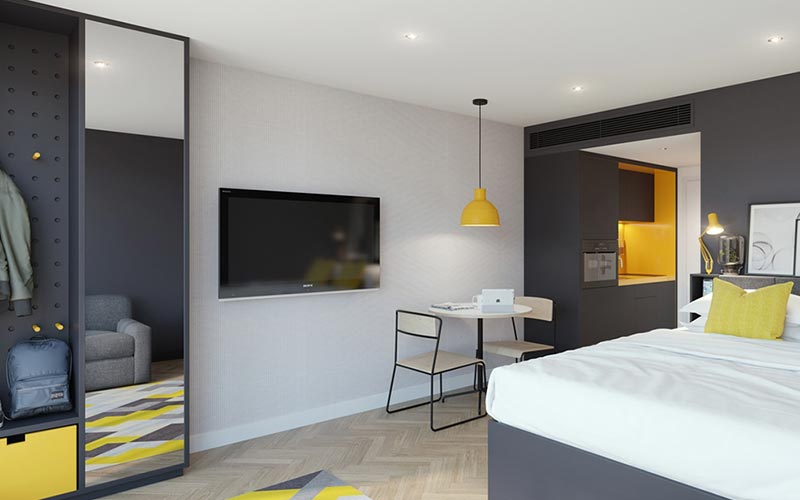 A grey and yellow themed room with a double bed, a wardrobe and a TV mounted on the wall