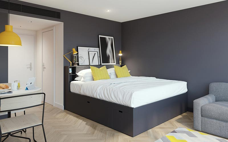 A double bed with a grey and yellow themed room with a double bed, seat and a small table