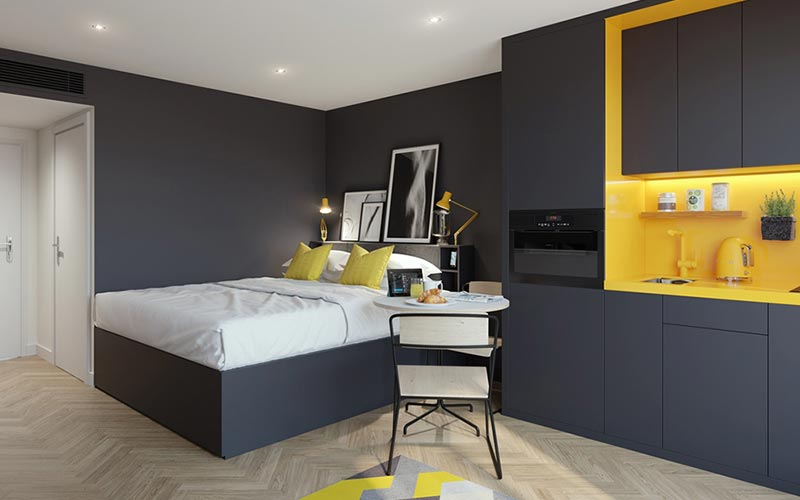 A double bed with a grey and yellow kitchen in the foreground