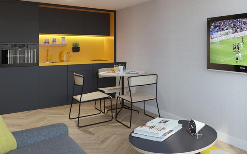 A double bed with a grey and yellow themed room with a kitchen, dining table and TV mounted on the wall