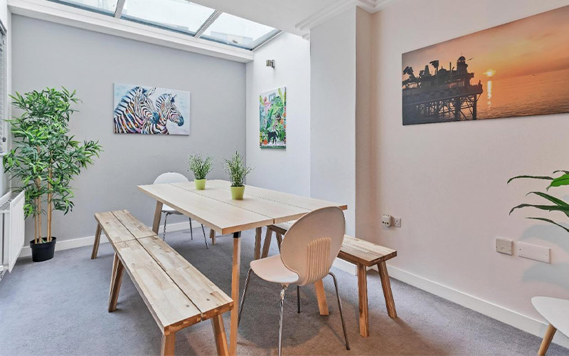 Image of a room with graffiti wall and bean bags with a black leather sofa and a black flat screen tv