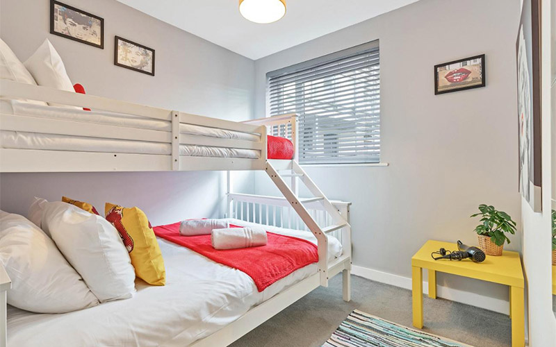 Image of a room with a double and single bunk bed with a lion portrait on the wall and a small square yellow table