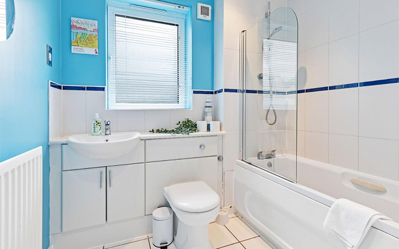 Image of a outdoor area with table and chairs and latern style lights going around the grey fence