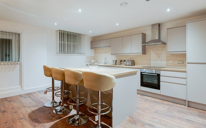 A kitchen layout with a breakfast bar and four chairs, cooking facilities and wood flooring