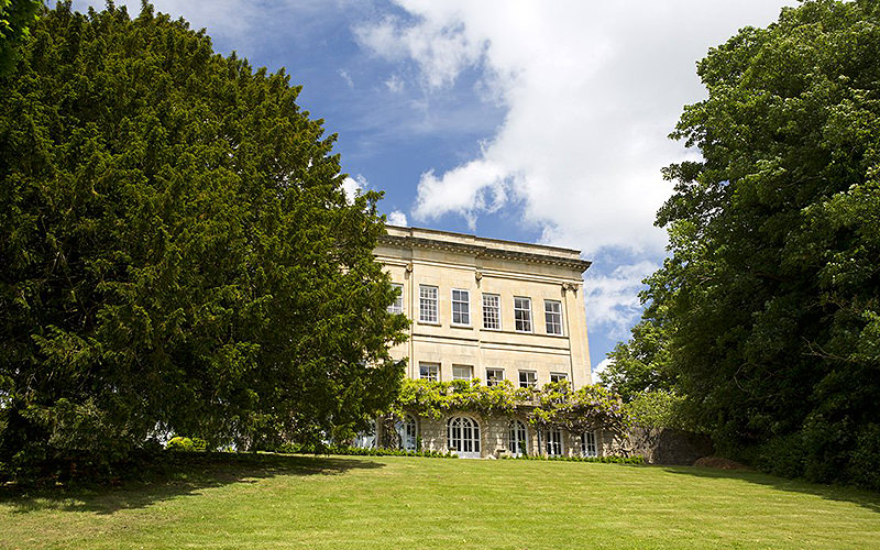 The exterior of Bailbrook House Hotel with trees and grass outside