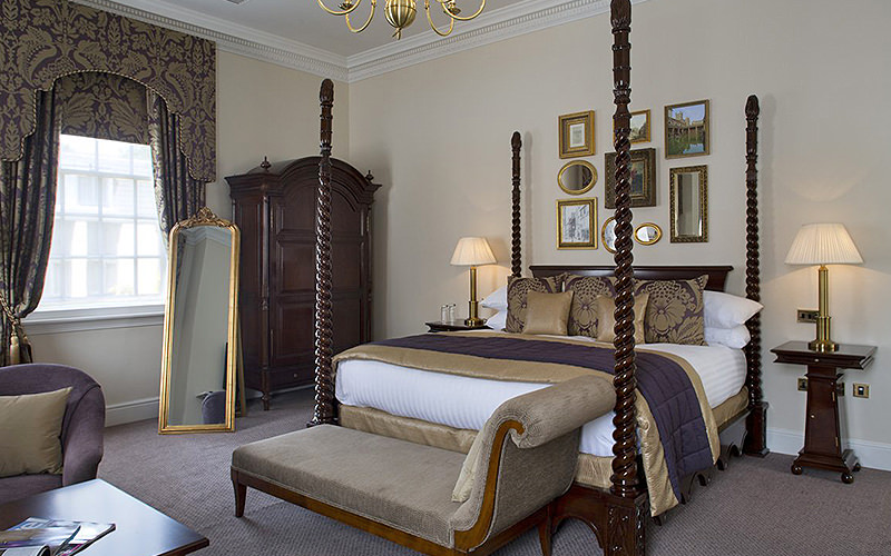A double bedroom with four poster bed in Bailbrook House Hotel