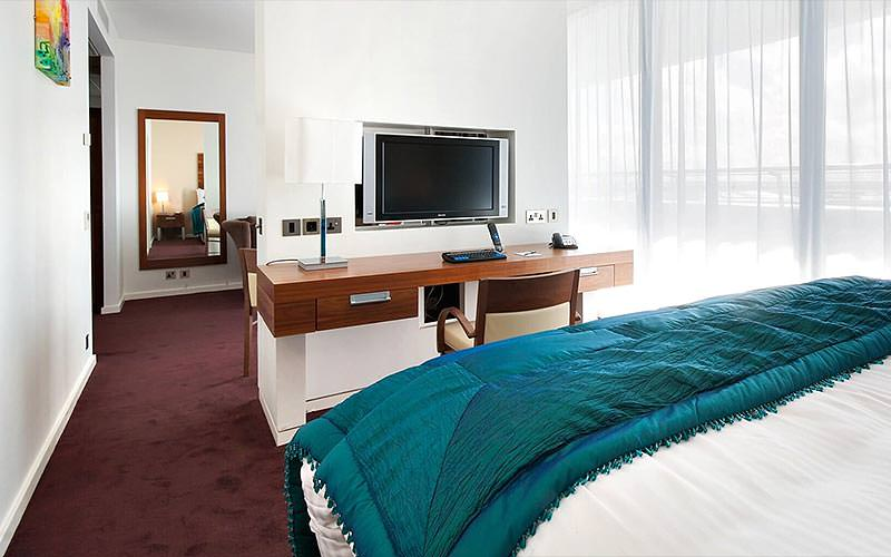 A double bed with a blue throw, facing a desk and TV in the wall