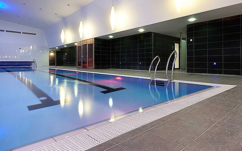 Indoor swimming pool with a black tiled wall