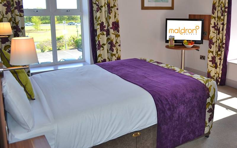 A double bed, topped with a purple throw and green cushions, facing a TV in the corner