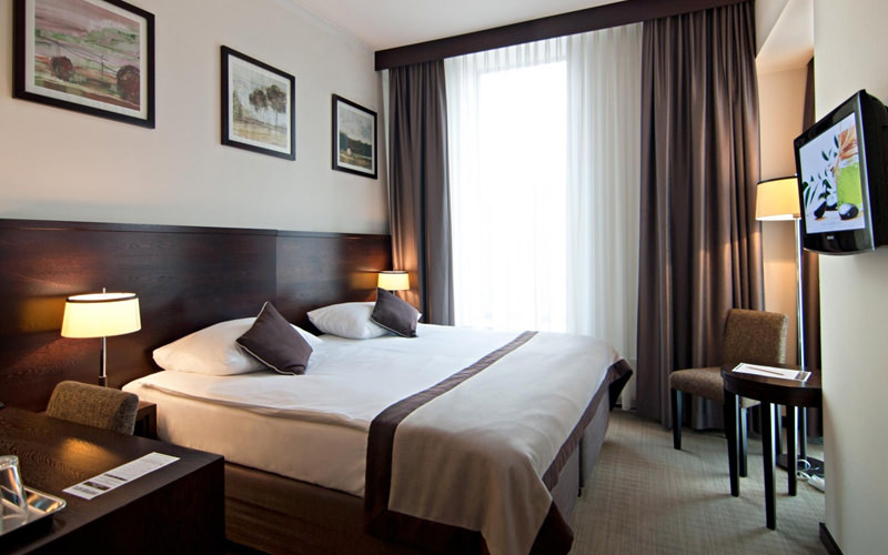 A hotel room with a large double bed