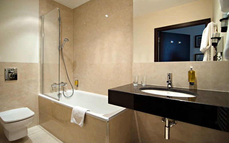 A hotel bathroom with a bath, shower and sink