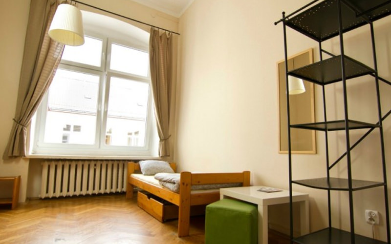 A hostel room with a small single bed