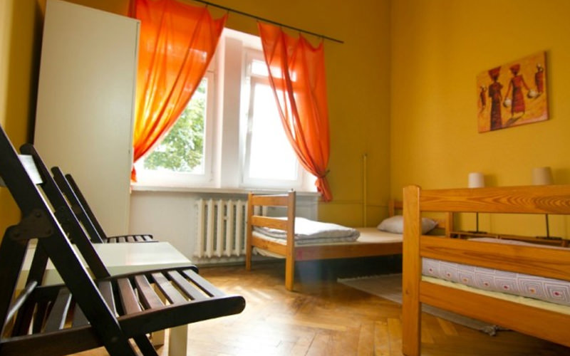 A hostel room with two single beds