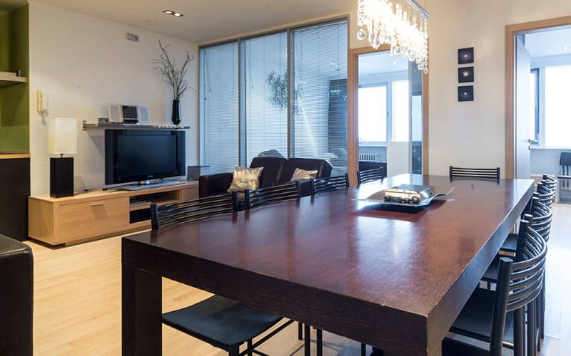 A large dining table and chairs and a lounge area with TV