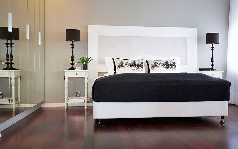 A double bed with vintage bedside tables and black lamps
