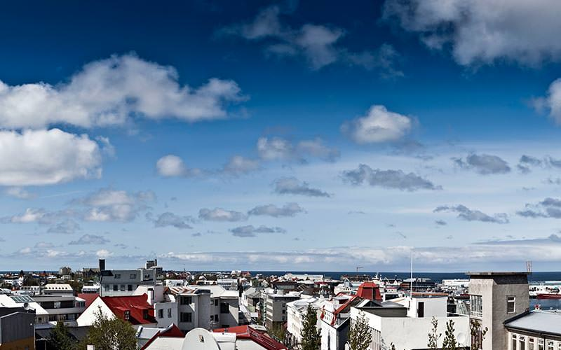 A view over the rooftops of Reykjavik with the sea visible in the background