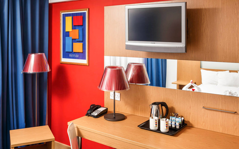 A desk in a hotel room with a TV above it