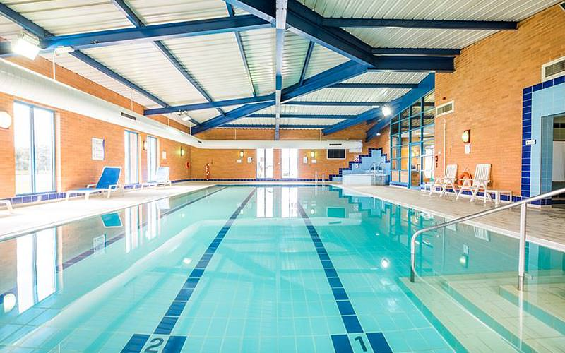 An indoor swimming pool with white sun loungers on the sides