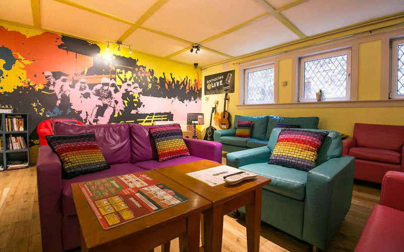 A lounge area in a hostel with several sofas and tables and brightly coloured walls