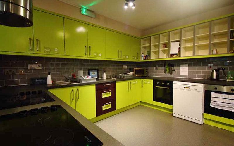 A bright green kitchen in a hostel