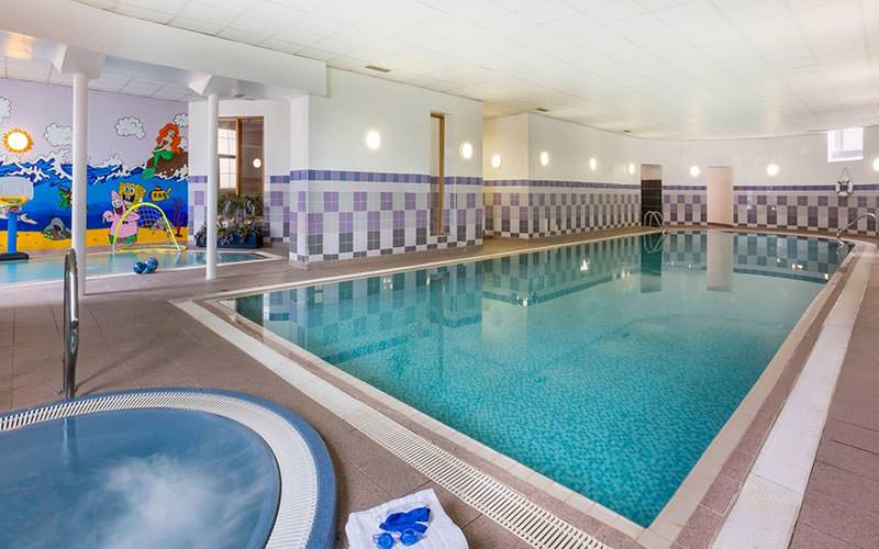 An indoor swimming pool with a Jacuzzi in the foreground